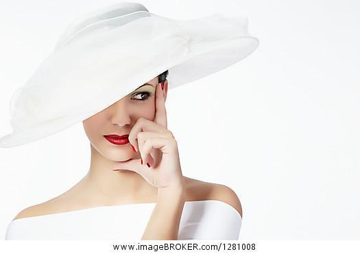 6e90d1ba0d5 Portrait of a young woman wearing a white summer hat and white dress with  her hand