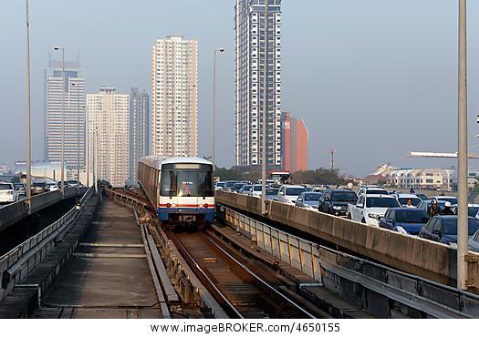 bts skytrain passes motorcade morning traffic jam on saphan taksin bridge bangkok thailand